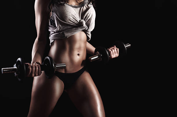 gym woman workout with dumbbells stock photo