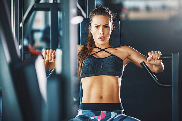 Gym workout. Closeup front view of attractive brunette working out on a chest press at a gym. SHe's looking at camera with hardworking, almost angry, expression. Toned shot. chest torso stock pictures, royalty-free photos & images