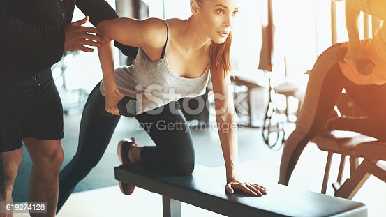 Closeup shot of two women doing dumbbell rows at a local gym. Leaning over workout bench and looking at a large mirror that is not in the frame.They are assisted by two unrecognizable male coaches, one of them not visible at all.