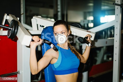 Young fitness woman working out in the gym wearing n95 face mask for protecting against Covid-19 infection. Shoulder machine exercise.
