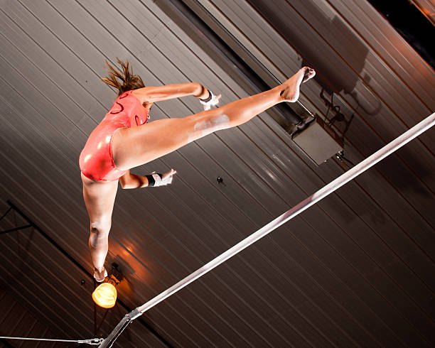 gymnast about to catch the bar (low angle view) - uneven parallel bars stock photos and pictures