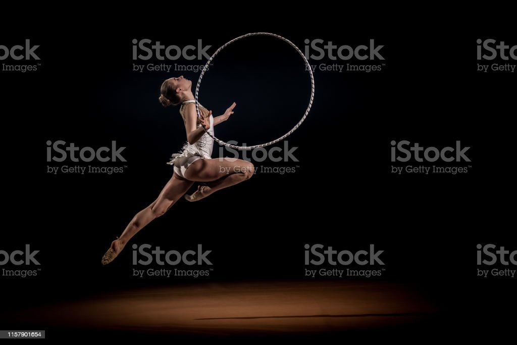 Female rhythmic gymnast rotating hoop and jumping.