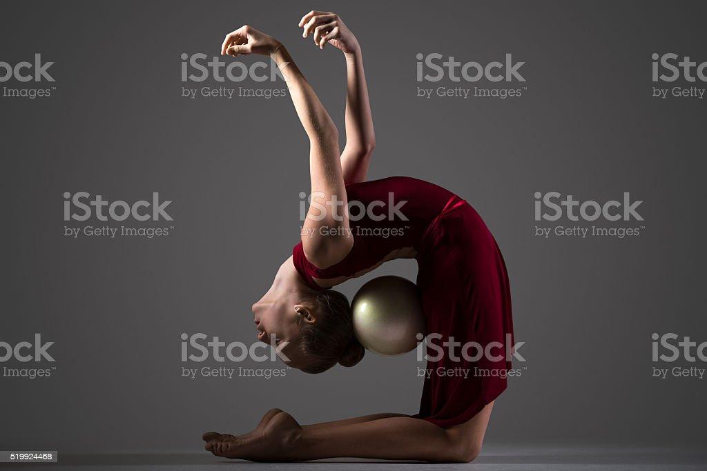 Gymnast girl bending backwards with ball stock photo