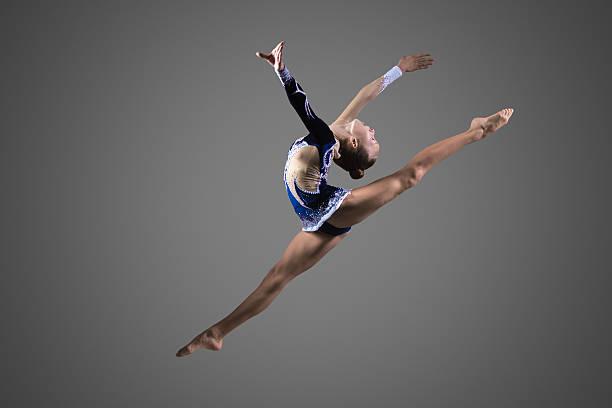 体操選手 ガールの空気して分割 - 体操競技 ストックフォトと画像