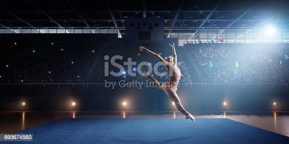 A gymnast girl makes a leap on a large professional stage. She is wearing a professional swimsuit for gymnastics. Behind her is a stadium with spectators.