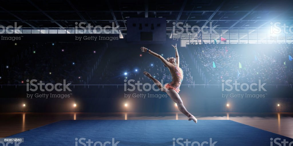 A gymnast girl makes a leap on a large professional stage stock photo
