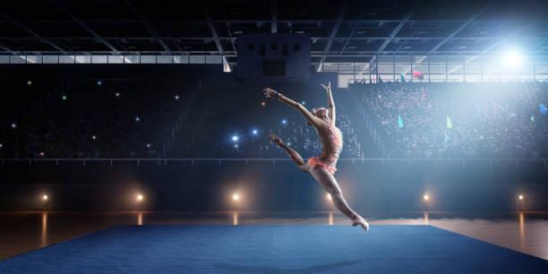 Eine Turnerin Mädchen macht einen Sprung auf eine große professionelle Bühne – Foto