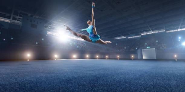 体操の女の子は、大規模なプロの舞台に飛躍 - 体操競技 ストックフォトと画像