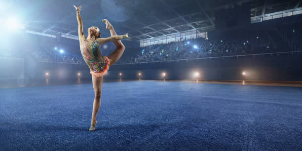 a gymnast girl makes performance on a large professional stage - sports championship stock photos and pictures