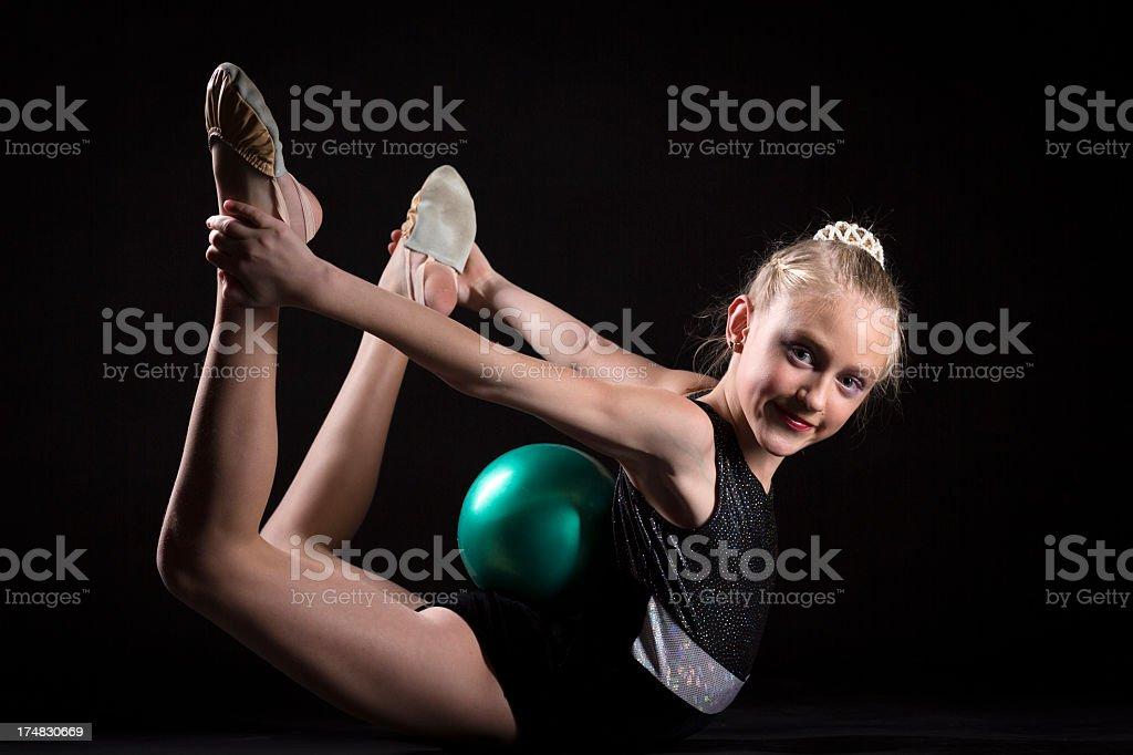 Gymnast girl with Rhythmic Ball on black background royalty-free stock photo