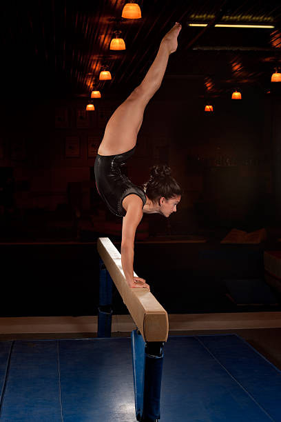 gymnast in a handstand on a balance beam in a dimly lit room - dimly stock pictures, royalty-free photos & images