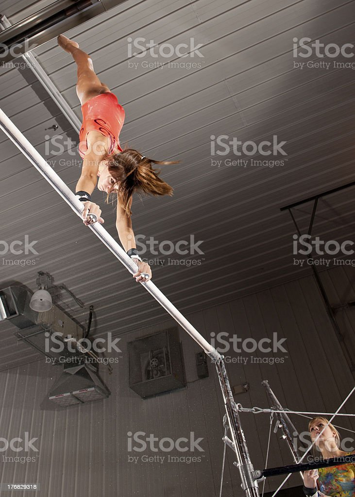 Gymnast in bars routine with teammate looking on royalty-free stock photo