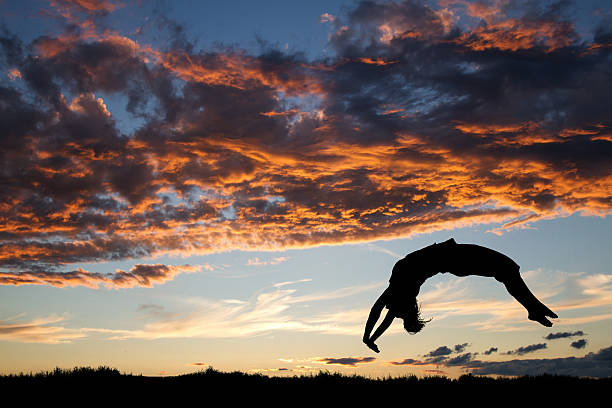 gymnast in sunset doing a back handspring stock photo