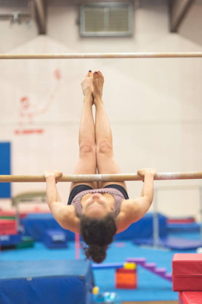 gymnast practices a routine on the uneven bars - uneven parallel bars stock photos and pictures