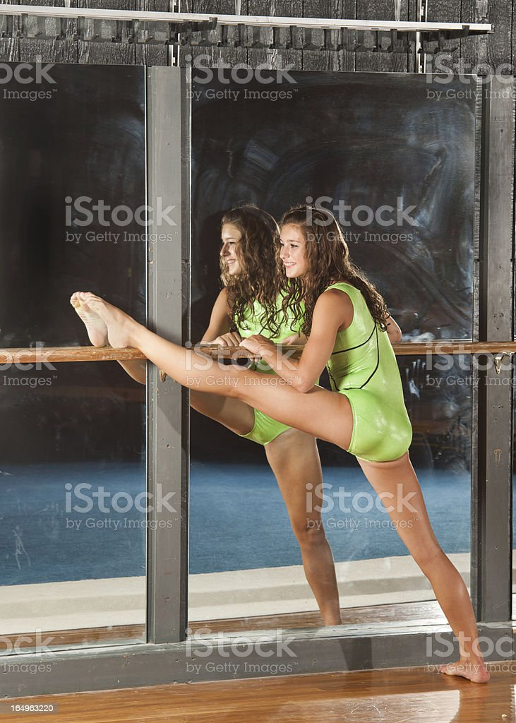 Gymnast stretches using bar along a mirror royalty-free stock photo