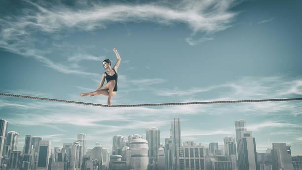 gymnast tightrope above city - trapez stock-fotos und bilder