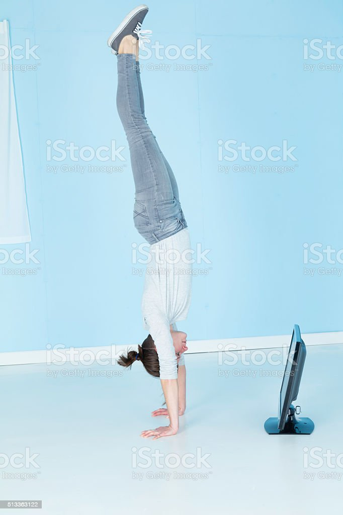 Gymnast Watching Television Whilst Doing A Handstand stock photo