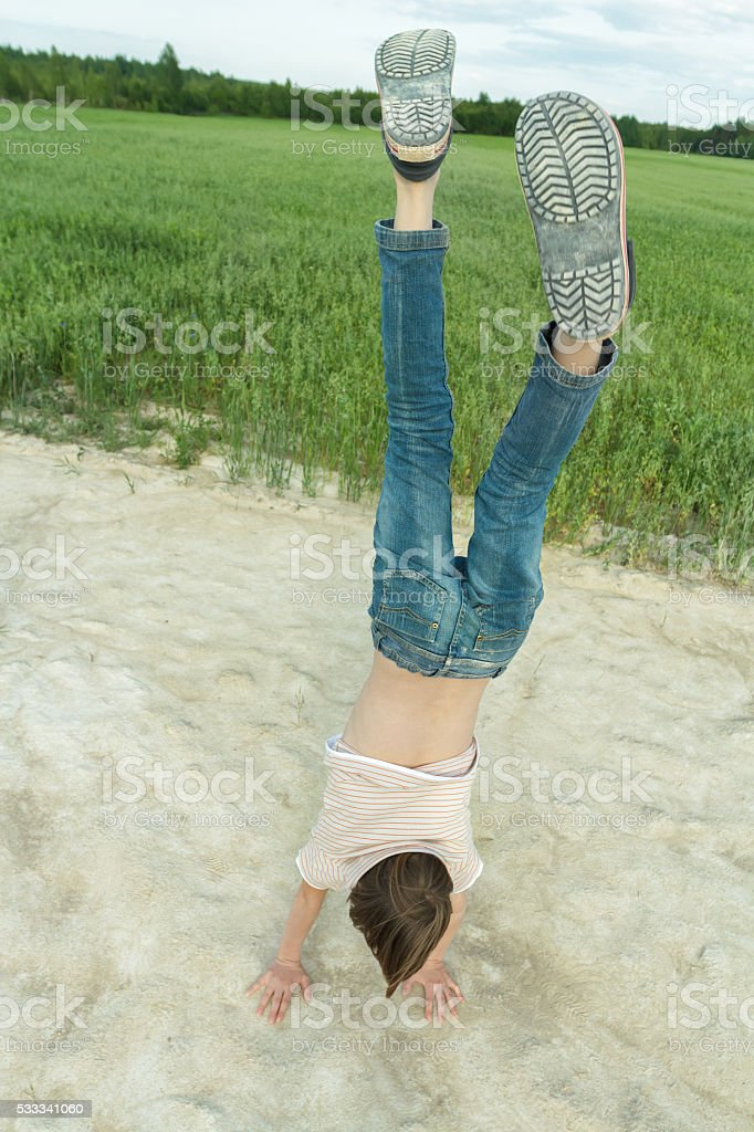 Gymnastic handstand of teenager on dirt road on field road stock photo