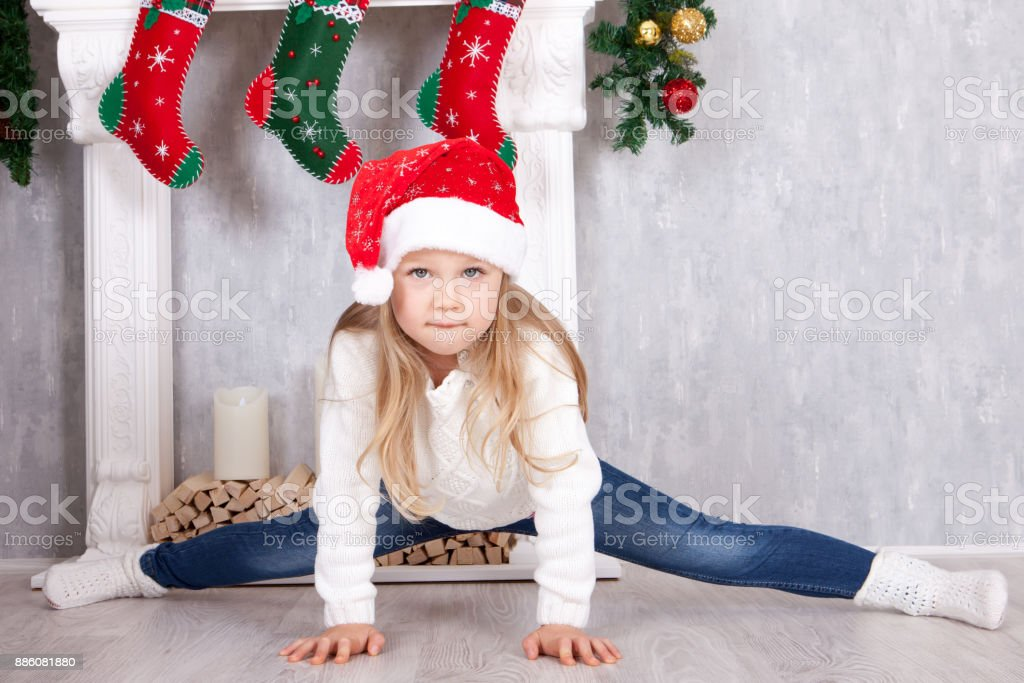 Gymnastic pose, stretch. Little blonde girl in the Santa hat, doing cross-twine exercising. Doing a full split in Christmas interior stock photo