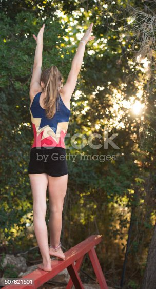 Rear view of concentrated fourteen year old gymnastic girl training on red balance beam outside in forest yard.