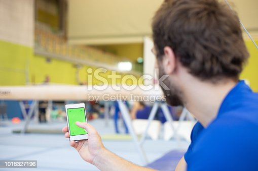 Gymnastics Athlete Using Mobile Phone with Greenscreen During Training Break.