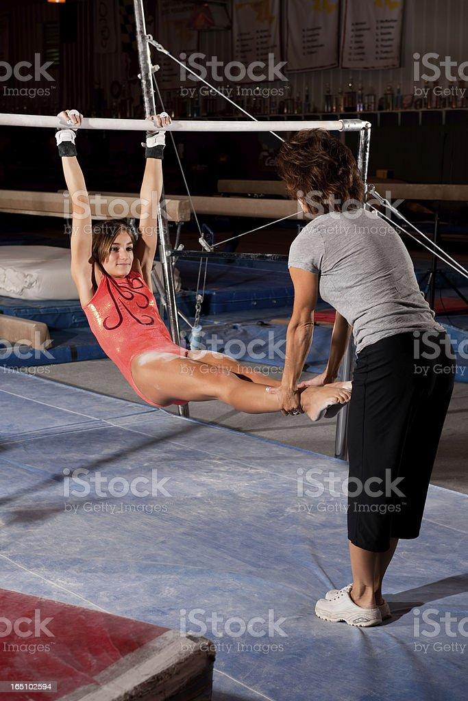 Gymnastics Coach Instructing Gymnast On Uneven Bars stock photo