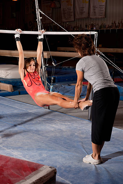 gymnastics coach instructing gymnast on uneven bars - uneven parallel bars stock photos and pictures