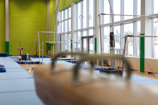 gymnastics equipment in an empty gym - uneven parallel bars stock photos and pictures