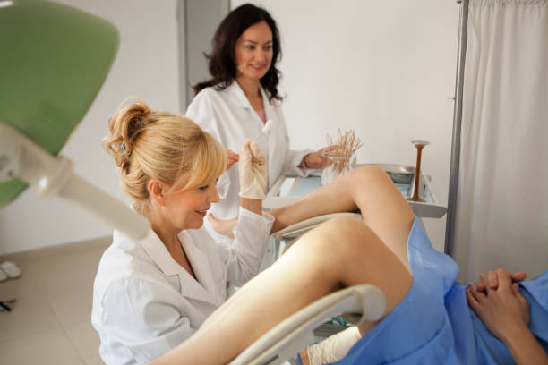 Gynaecologist examining a patient Gynaecologist examining a patient with a microscope pap smear stock pictures, royalty-free photos & images