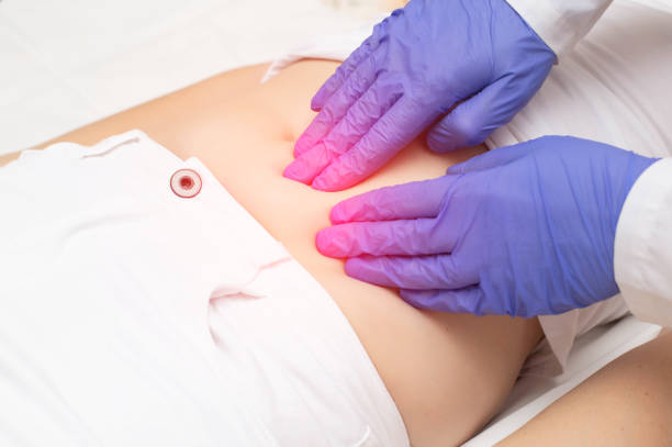 A gynecologist doctor probes the lower abdomen of a girl who has pain and inflammation of the reproductive system. Ovarian cyst, endometriosis, pregnancy pathology A gynecologist doctor probes the lower abdomen of a girl who has pain and inflammation of the reproductive system. Ovarian cyst endometriosis stock pictures, royalty-free photos & images