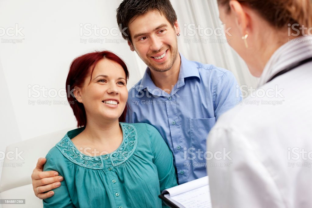 Gynecologist Talking To Pregnant Woman and her husband royalty-free stock photo
