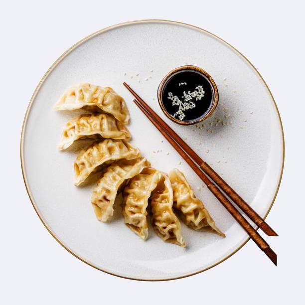 Gyoza dumplings on plate, chopsticks and soy sauce isolate stock photo