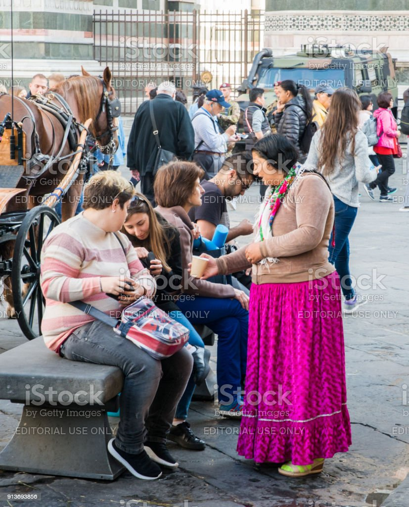 Gypsie woman successfully begs tourists in front of the Florence Cathedral in Tuscany, Italy stock photo