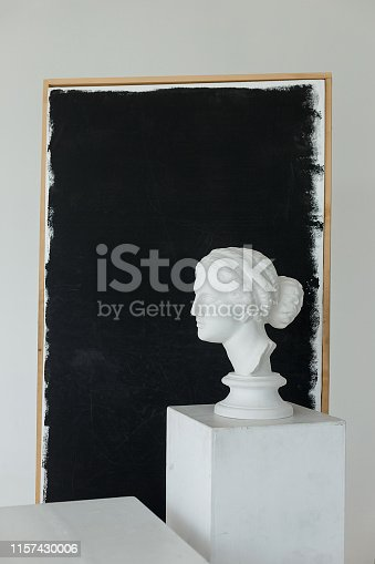 665487076istockphoto gypsum ancient girl head statue on large white cube in studio with black flag on a background with a copyspace for text 1157430006