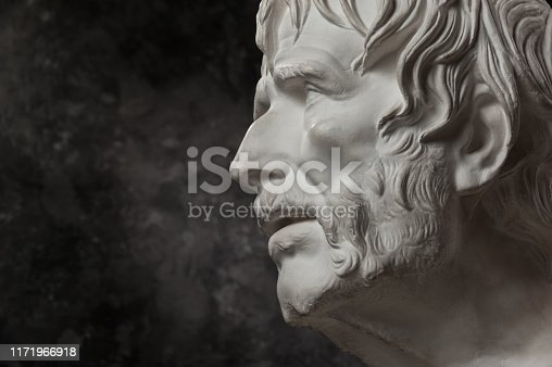 istock Gypsum copy of ancient statue Seneca head on dark textured background. Plaster sculpture man face. 1171966918