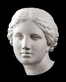 White gypsum copy of ancient statue of Venus de Milo head for artists isolated on a black background. Plaster sculpture of woman face.