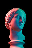 Gypsum copy of ancient statue of Venus de Milo head for artists isolated on a black background. Plaster sculpture of woman face. Multi color toned.