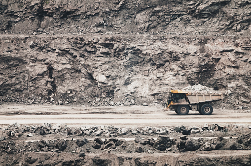 excavator digs against the sky in summer