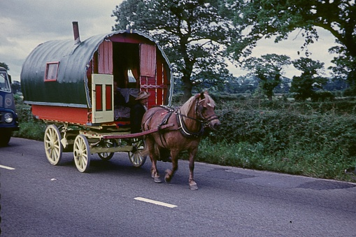 Central England, UK, 1958. Gypsy wagon with owner on a north west English country road.