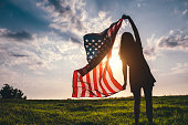 Gypsy young woman waving USA flag outdoor.
