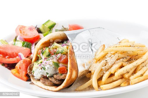 Gyro pita sandwich with middle eastern fries and salad close up on white background