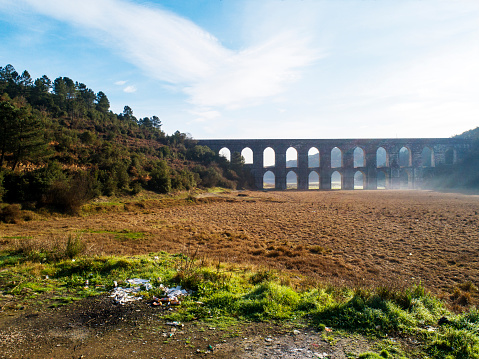 Istanbul,Turkey-December 06,2021:Güzelce Aqueduct is a historical aqueduct within the boundaries of Cebeci neighborhood of Sultangazi district of Istanbul. Its height is 29.5; The arch is 155 meters long and 8; It has 11 eyes on the top. The arch walls are 5.4 at the bottom; At the top, it is 2.6 meters thick. The building, which is the work of Mimar Sinan; It is in the basin of the Alibeyköy Dam today.