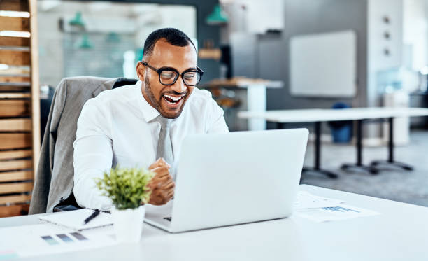 Ha! I knew it! Cropped shot of a handsome young businessman sitting alone in his office and feeling excited while working on his laptop excitment stock pictures, royalty-free photos & images