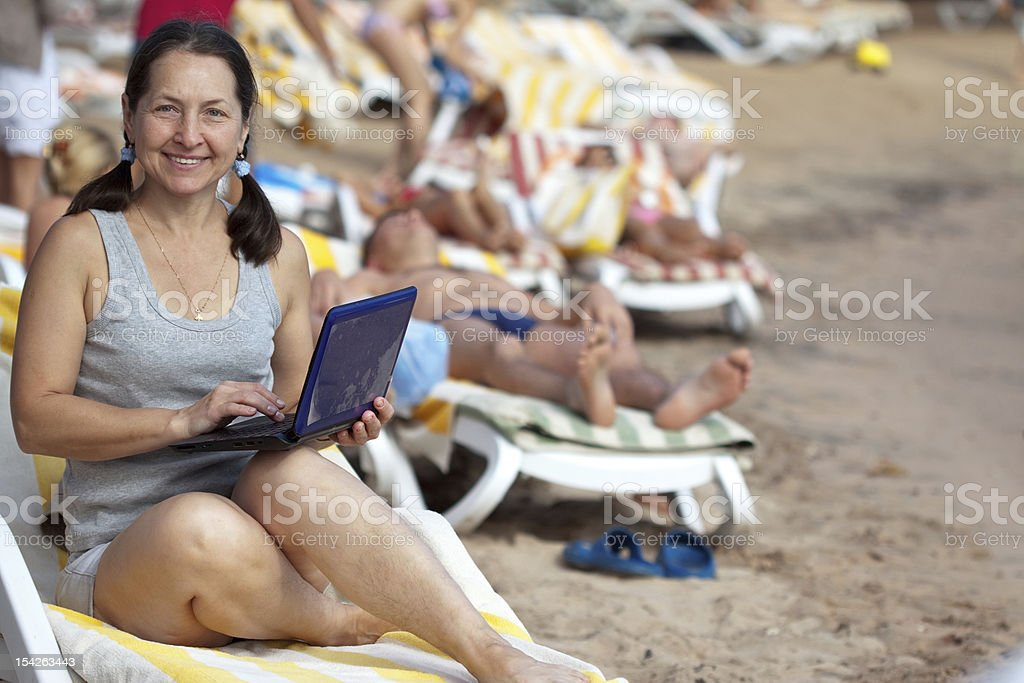 Ha ppy mature woman  with laptop at resort royalty-free stock photo
