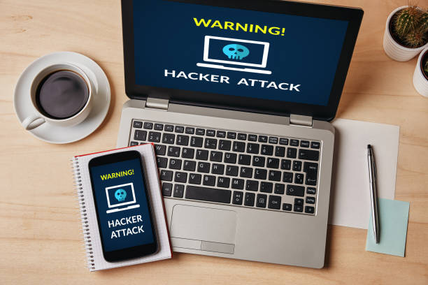 Hacker attack concept on laptop and smartphone screen stock photo