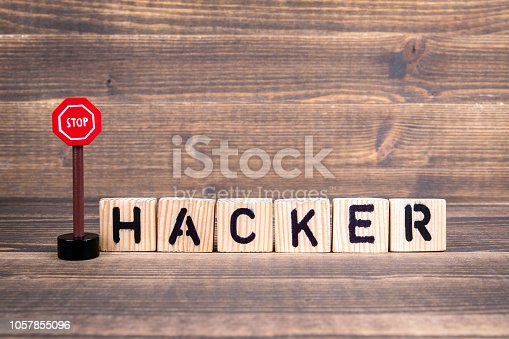 istock Hacker concept. Wooden letters with road sign 1057855096