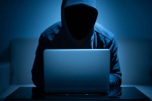 Hacker dark face using laptop Hacker dark face using laptop in the dark room computer crime stock pictures, royalty-free photos & images