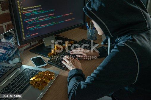 istock hacker doing bitcoin virus robbery thru malware. 1041525456