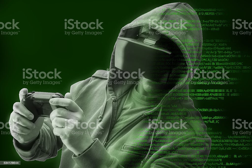Hacker / gamer wearing a VR Helmet surrounded by green code - Stock image .