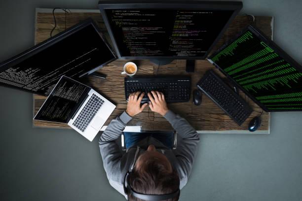 Hacker Hacking Multiple Computers On Desk stock photo